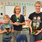 Students at the Peonan Point School  holding planters made with recycled plastic bottles